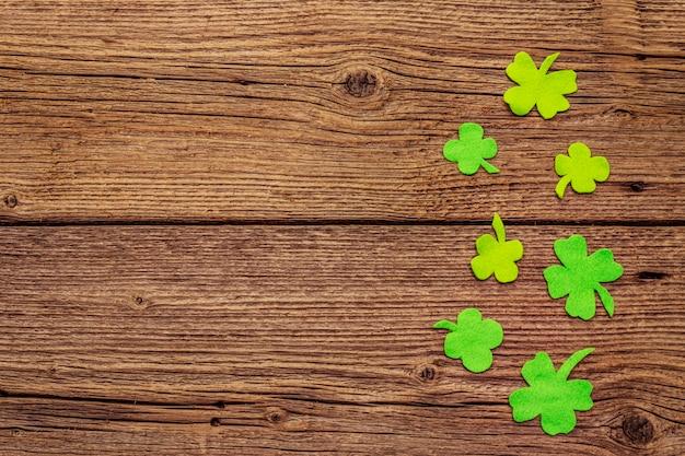Folhas de trevo de feltro no fundo de madeira velho. símbolo de boa sorte, conceito do dia de st.patrick Foto Premium