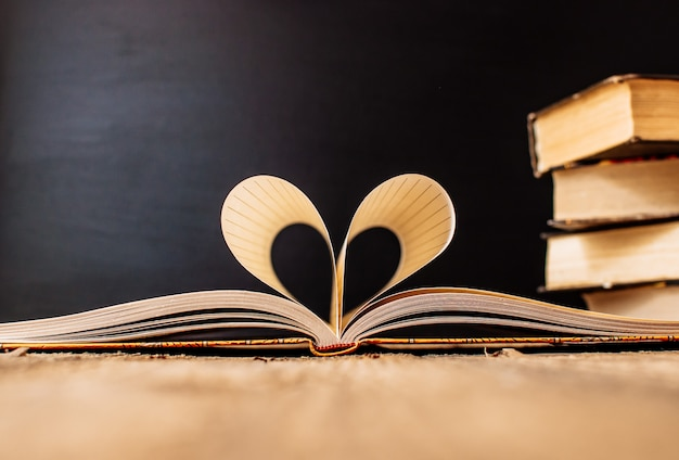Folhas de um caderno em uma gaiola envolto em forma de coração Foto Premium