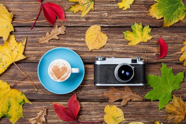 Folhas do outono, câmera e copo de café na tabela de madeira. Foto Premium