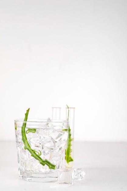 Folhas frescas de aloe vera e suco de aloe vera em vidro no fundo branco Foto Premium