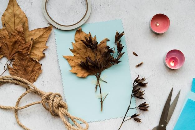 Folhas secas de outono em papel azul com string e velas acesas sobre o pano de fundo branco Foto gratuita