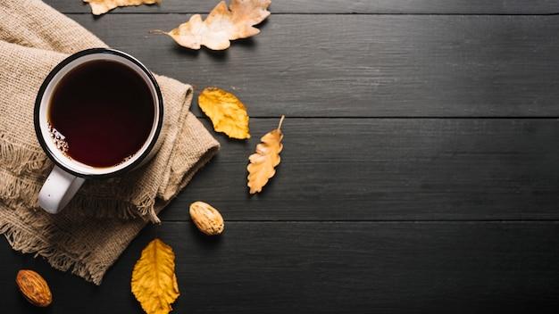 Folhas secas e miolo perto de bebida e tecido Foto gratuita