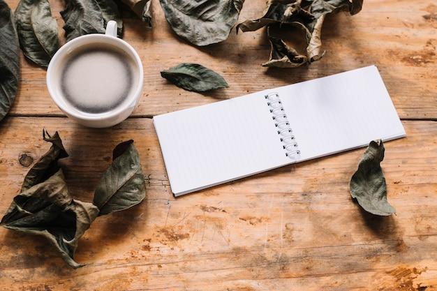 Folhas secas, xícara de café e notebook em fundo de madeira Foto gratuita