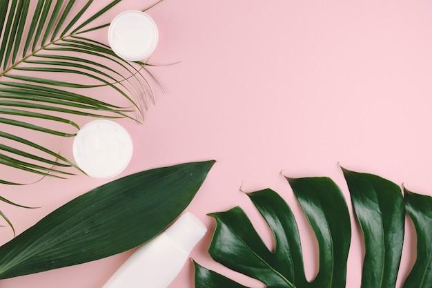 Folhas tropicais de vista superior com ferramentas de beleza e cosméticos Foto gratuita
