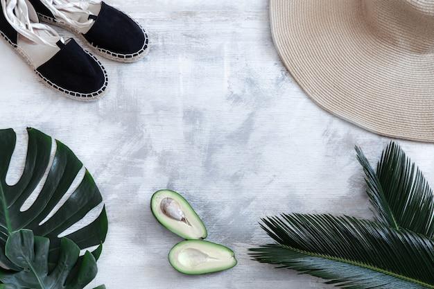 Folhas tropicais em um fundo branco com acessórios de verão conceito de férias de verão e recreação. bandeira de cartaz, modelo de cartão postal. Foto gratuita