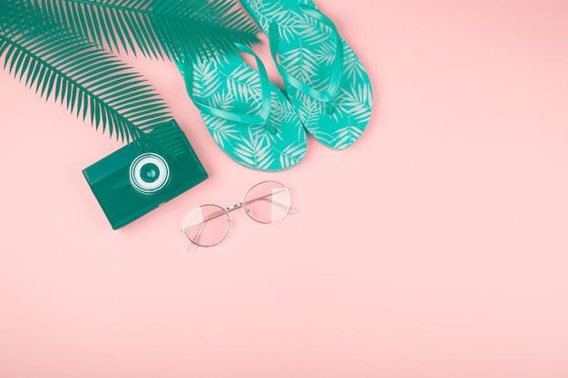 Folhas verdes; câmera; óculos de sol e par de chinelos contra fundo rosa Foto gratuita