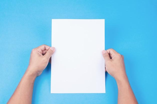 Folheto em branco com placa na mão no fundo azul. maquete para design Foto Premium