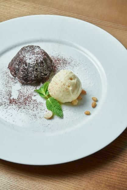 Fondant de chocolate com uma bola de sorvete de baunilha num prato branco sobre uma mesa de madeira. sobremesa de dar água na boca no café da manhã Foto Premium