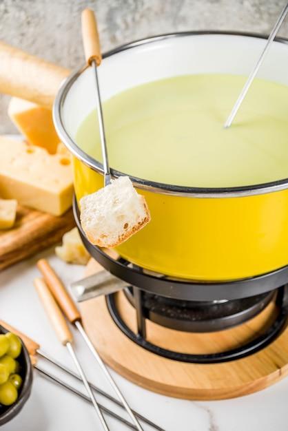 Fondue suíço gourmet em panela de fondue tradicional, com garfos, queijos diversos, azeitonas, pão e uva Foto Premium