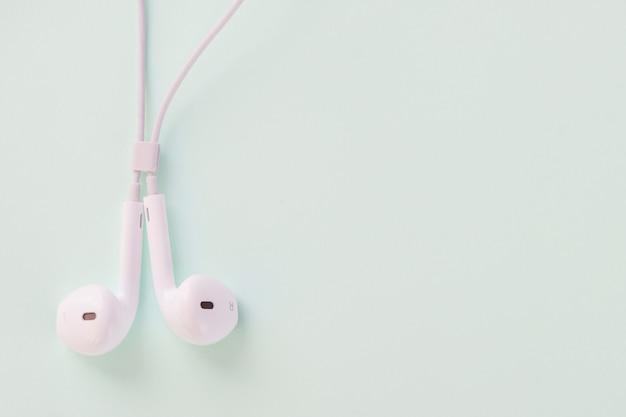 Fone de ouvido branco em fundo pastel doce Foto Premium