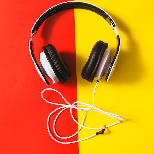 Fone de ouvido branco sobre o fundo vermelho e amarelo dual Foto gratuita