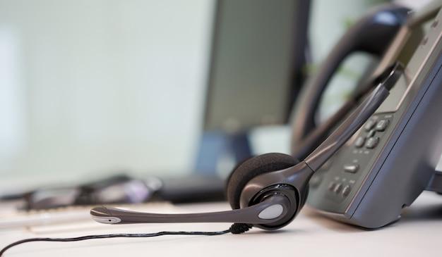 Fone de ouvido com dispositivos de telefone na mesa do escritório Foto Premium