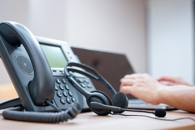 Fone de ouvido com turva da mão de funcionário de call center trabalhando na sala de operação Foto Premium