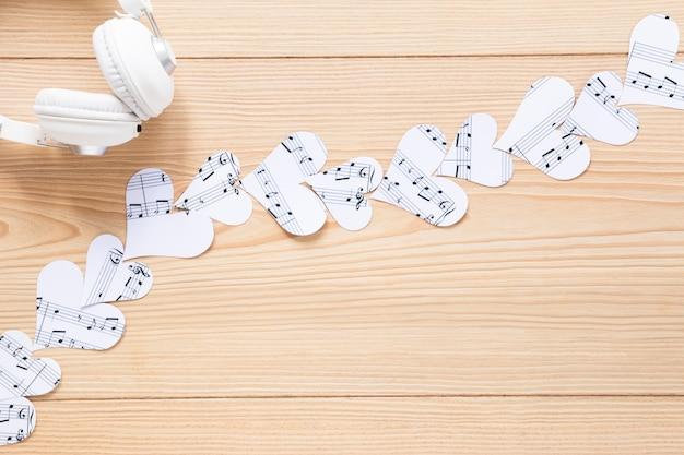 Fone de ouvido com vista superior com corações de papel Foto gratuita