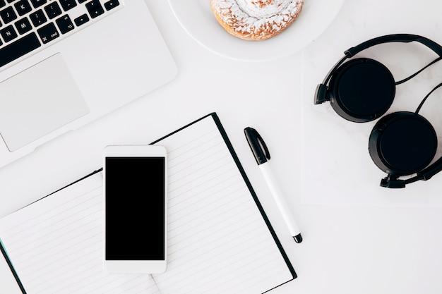 Fone de ouvido; computador portátil; celular; diário; caneta e comida cozida no fundo branco Foto gratuita