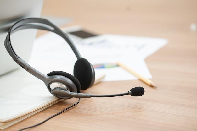 Fone de ouvido do call center na sala de escritório do computador com o conceito de relatório financeiro. Foto Premium
