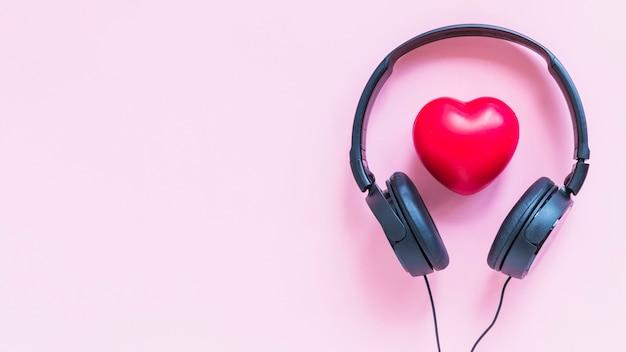 Fone de ouvido em torno da forma de coração vermelho contra o pano de fundo rosa Foto gratuita