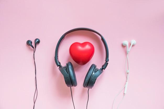 Fone de ouvido em torno do coração vermelho entre dois fones de ouvido contra o pano de fundo rosa Foto gratuita