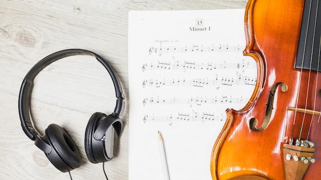 Fone de ouvido; lápis; e violino sobre nota musical em fundo de madeira Foto gratuita