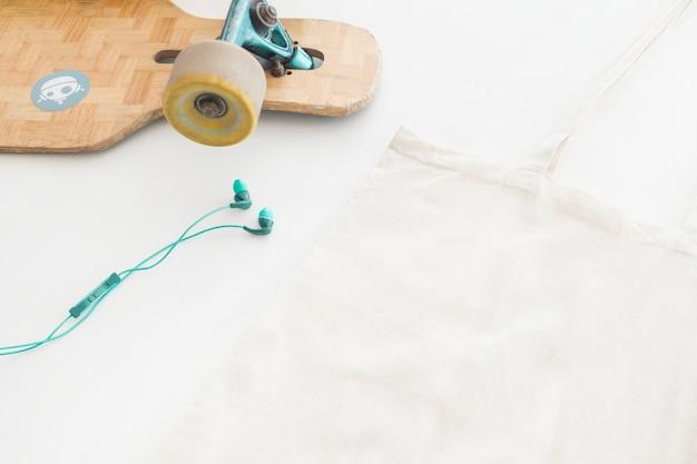 Fone de ouvido, skatingboard e bolsa no fundo branco Foto gratuita