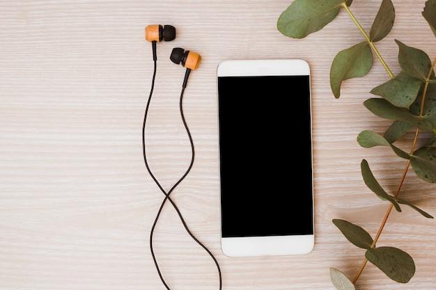 Fone de ouvido; telefone celular e folhas no fundo de madeira Foto gratuita