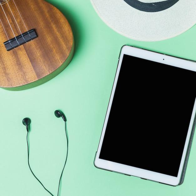 Fone de ouvido; violão; chapéu e tablet digital em fundo turquesa Foto gratuita