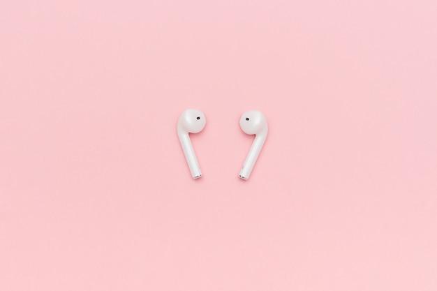 Fones de ouvido bluetooth sem fio branco sobre fundo rosa pastel Foto Premium