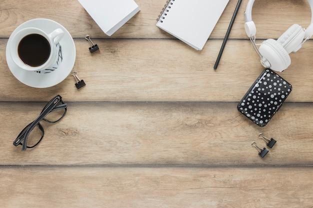 Fones de ouvido de papelaria e café na mesa de madeira Foto gratuita