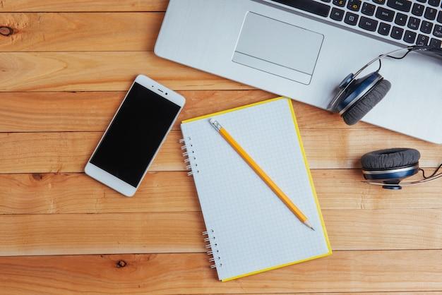 Fones de ouvido do notebook laptop e olivchem em uma luz de madeira. Foto Premium
