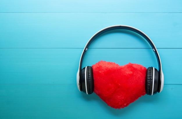 Fones de ouvido e coração escutando música de forma no fundo de madeira azul Foto Premium