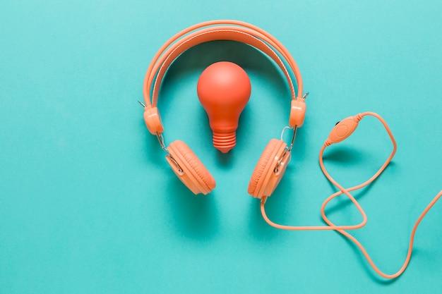 Fones de ouvido e lâmpada na superfície colorida Foto gratuita