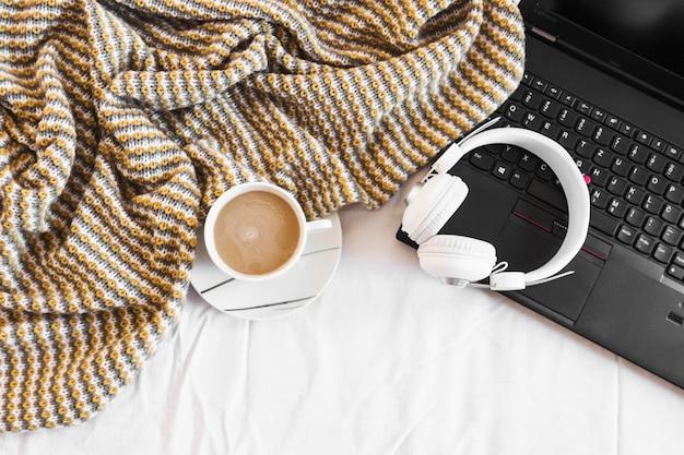 Fones de ouvido e laptop perto de cobertor e café Foto gratuita