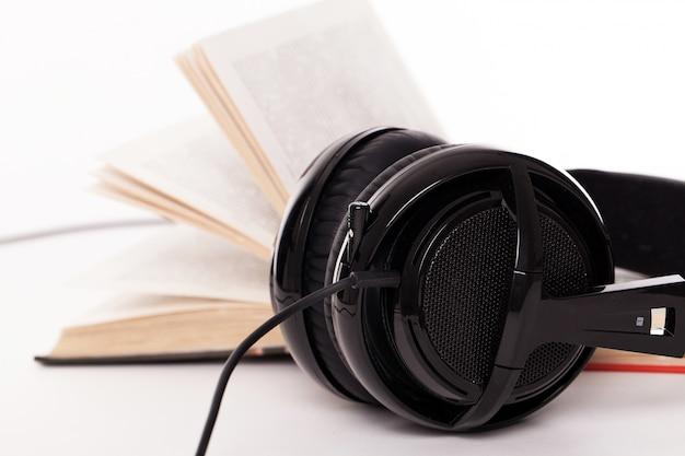 Fones de ouvido e livro sobre um fundo branco Foto gratuita