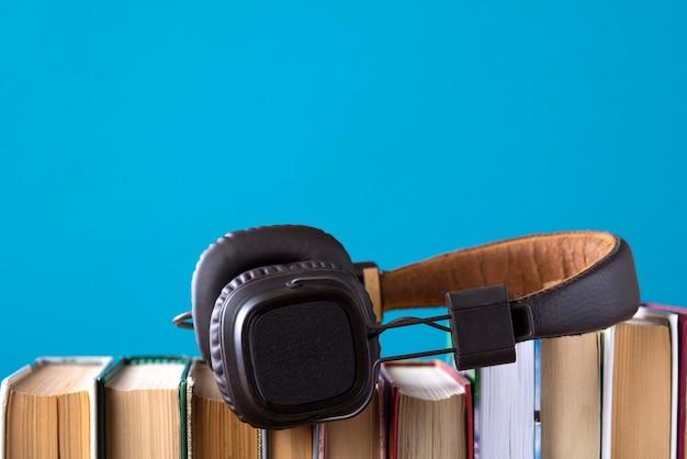 Fones de ouvido e livros, mas contra livros em áudio azuis, ouvindo um livro Foto Premium