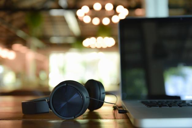 Fones de ouvido e portátil pretos na tabela de madeira na cafetaria do borrão. tema de criação de música digital. Foto Premium