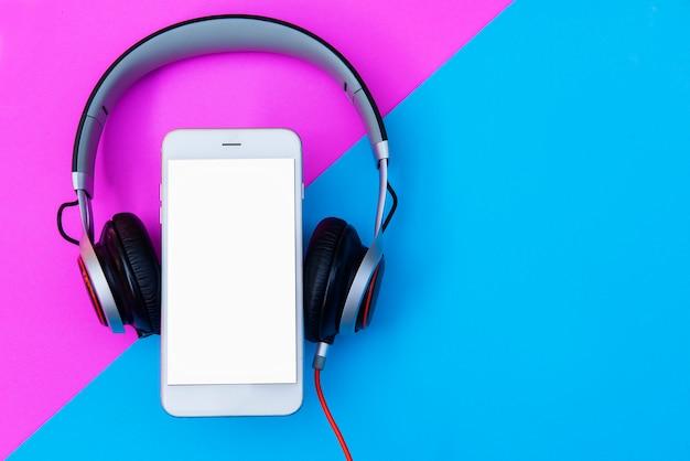 Fones de ouvido e smartphones leigos planos sobre um fundo pastel de cor duotone e espaço da cópia. Foto Premium