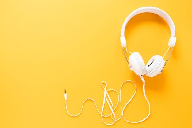 Fones de ouvido em fundo amarelo com espaço de cópia Foto gratuita