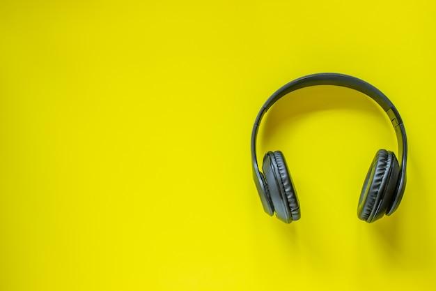 Fones de ouvido pretos em um fundo amarelo. conceito mínimo. postura plana. Foto Premium