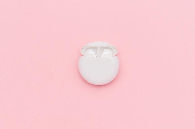 Fones de ouvido sem fio brancos de bluetooth no caso de carregamento no fundo de papel cor-de-rosa. Foto Premium
