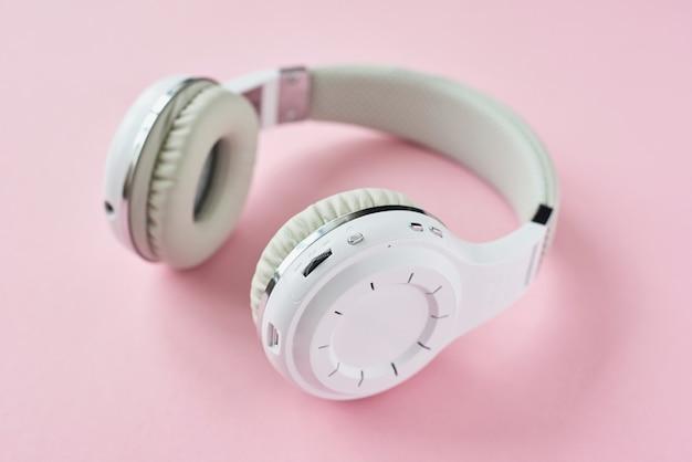 Fones de ouvido sem fio brancos sobre um fundo azul pastel Foto Premium