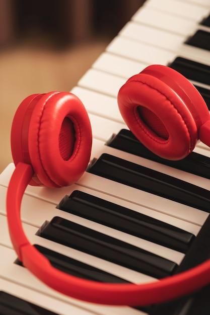 Fones de ouvido vermelhos sobre o teclado sintetizador Foto Premium