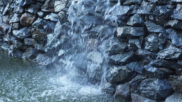 Fonte como cachoeira artificial que flui ao longo das pedras do rock do norte da caucasiana. Foto Premium