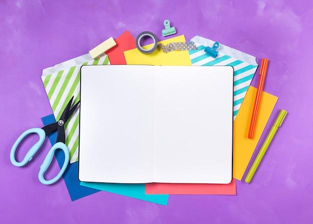 Fontes de escritório brilhantes, artigos de papelaria da escola, bloco de notas branco na tabela, fundo roxo. volta ao conceito de escola. vista do topo. copie o espaço. Foto Premium