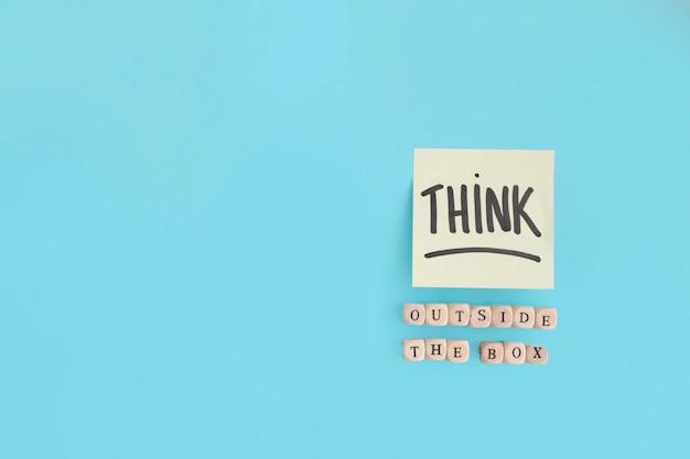 Fora da caixa de texto feito com blocos de madeira e acho que o texto na nota adesiva Foto gratuita