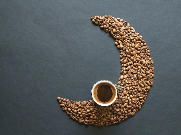 Forma crescente feita de grãos de café e uma xícara de café preto. vista do topo. Foto Premium