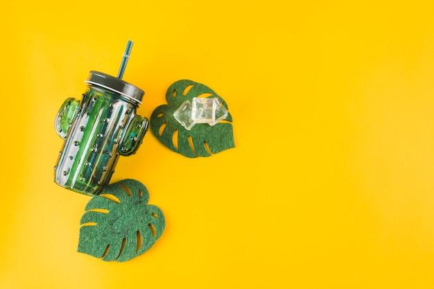 Forma de cacto jar com cubos de gelo e folhas de monstera artificial sobre fundo amarelo Foto gratuita