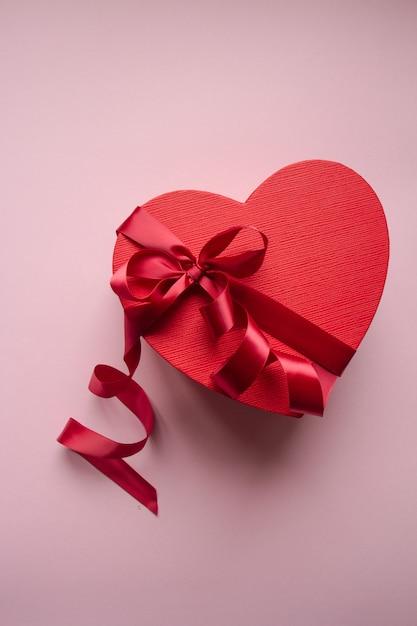 Forma de coração de caixa de presente vermelha com fita vermelha Foto Premium