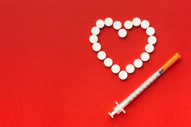 Forma de coração de comprimidos e seringa Foto gratuita