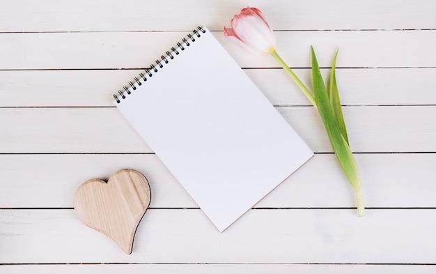 Forma de coração de madeira; bloco de notas em branco em espiral e tulipa na mesa de madeira Foto gratuita
