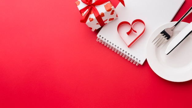 Forma de coração de papel no notebook com placa e presente para dia dos namorados Foto gratuita